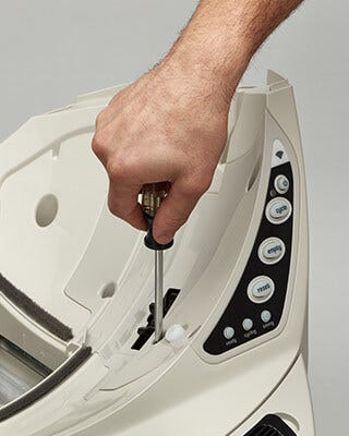 hand using a screwdriver on the Litter-Robot base